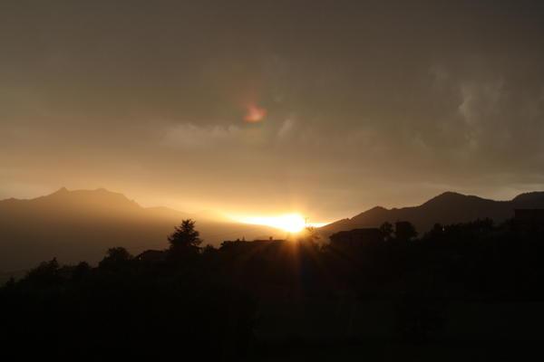 Les derniers rayons du soleil couchant se frayent un chemin entre les nuages d'orage et la crête d'espréau.